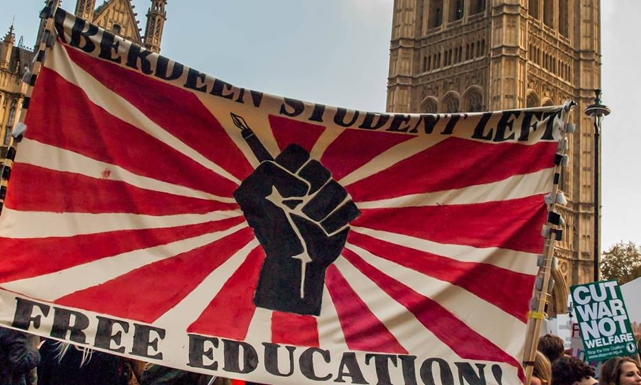 A photograph of an Aberdeen Student Left banner at a demonstration in London. The banner says Aberdeen Student Left Free Education on it and features a black raised fist holding a fountain pen on a red and white sunburst background.